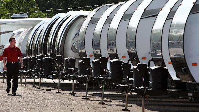 In this Tuesday, June 18, 2013, photo, Rusty Eckstein of Mount Comfort RV, in Greenfield, Ind. walks past a line of travel trailers at the dealership. The Commerce Department reports on business orders for durable goods in June on Thursday, July 25, 2013. (AP Photo/The Indianapolis Star, Charlie Nye)