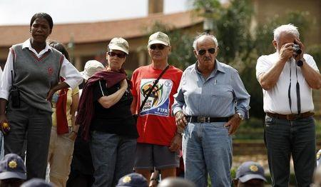 A group of foreign tourists watch as National Taxi Alliance members protest outside the Union Buildings in Pretoria