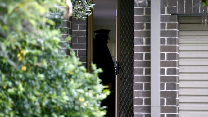 New South Wales police officer talks to people in a house after a man was arrested during early morning raids in western Sydney, Australia