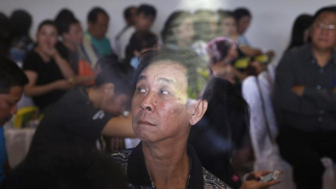 Family members of passengers onboard AirAsia flight QZ8501 wait for news of the airplane in Surabaya