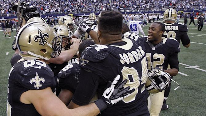 The New Orleans Saints celebrate at the end of overtime against the Dallas Cowboys at an NFL football game on Sunday, Dec. 23, 2012, in Arlington, Texas. The Saints won 34-31. (AP Photo/Brandon Wade)