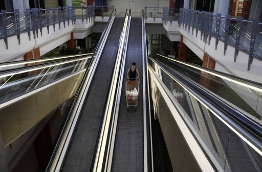 <p>A woman stands on an escalator with her shopping trolley at a partially empty supermarket in Nicosia on June 21. Cyprus asked for a eurozone rescue, the same day Spain formally requested a banking bailout.</p>