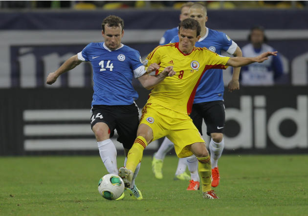 Konastantin Vassiljev, left, of Estonia and Costin Lazar, right, of Romania challenge for the ball during the World Cup Group D qualifying soccer match at the National Arena stadium in Bucharest, Roma