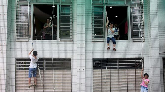 Children and parents rope down a building as they participate in a safety education activity to experience a fire escape, at a school in Guangzhou