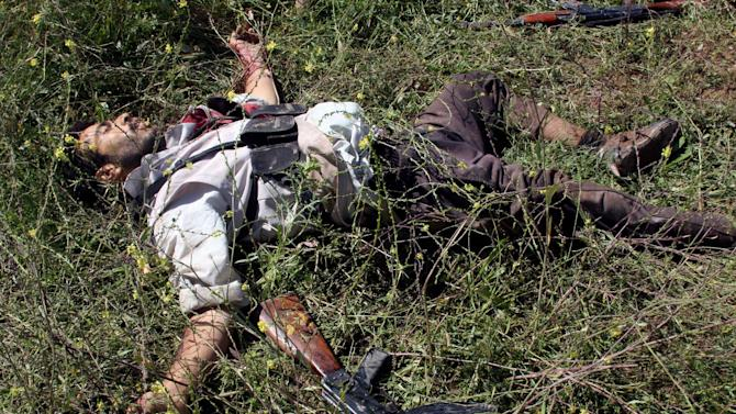 The body of a gunman killed during clashes with Iraqi security forces lies on the ground in Hawija, 150 miles (240 kilometers) north of Baghdad, Iraq, Tuesday, April 23, 2013. Iraqi security forces backed by helicopters raided a Sunni protest camp before dawn Tuesday, prompting clashes that killed scores of people in the area and significantly intensified Sunni anger against the Shiite-led government. (AP Photo)