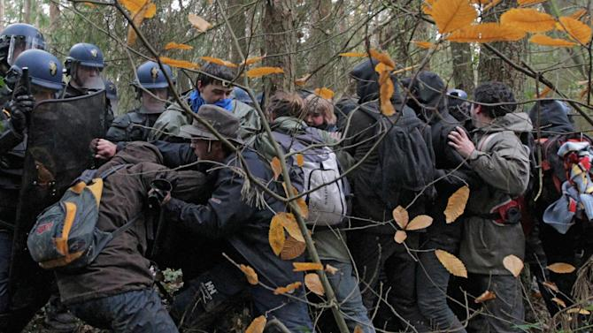 Protestors confront French riot police during the evacuation of protestors on land that will become the new airport in Notre-Dame-des-Landes, western France  Saturday Nov. 24, 2012. The protestors are opposing the building of a new airport there. In a muddy, rainy standoff starting early Friday, protesters responded to police attempts to remove them by hurling sticks, stones and gasoline bombs. For two weeks, protesters have illegally occupied the site of the planned Notre-Dame-Des-Landes airport set to start operating in 2017. (AP Photo/ Laetitia Notarianni)