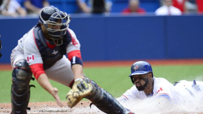 Toronto Blue Jays' Jose Reyes slides into home to score on a sacrifice fly by Jose Bautista as Boston Red Sox catcher Sandy Leon waits for the throw during the sixth inning of a baseball game Wednesday, July 1, 2015. (/Frank Gunn/The Canadian Press via AP)