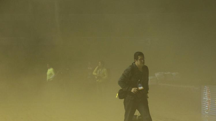 A photographer leaves the court amidst smoke after a transformer exploded in Mexico City