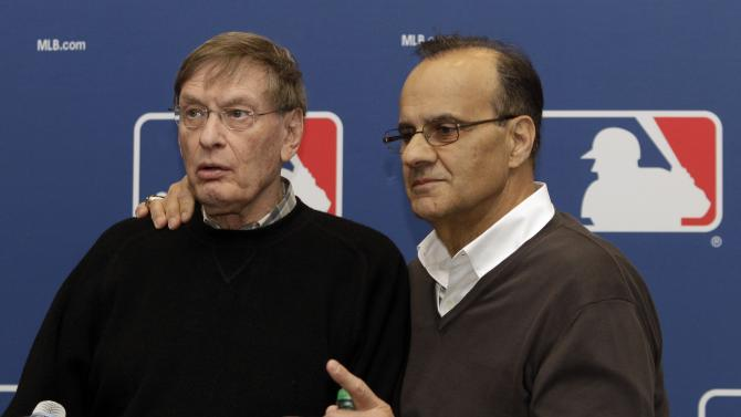 FILE - In this Feb. 26, 2011 file photo, Joe Torre, right,  embraces Major League Baseball commissioner Bud Selig during a news conference to announce Torre's new position as Major League Baseball's executive vice president of baseball operations,  in Scottsdale,  Ariz.  Torre has resigned as Major League Baseball's executive vice president for baseball operations to join a group trying to buy the Los Angeles Dodgers. (AP Photo/Marcio Jose Sanchez, File)