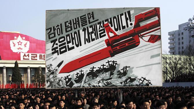 """North Koreans attend a rally to support a statement given on Tuesday by a spokesman for the Supreme Command of the Korean People's Army vowing to cancel the 1953 cease-fire that ended the Korean War as well as boasting of the North's ownership of """"lighter and smaller nukes"""" and its ability to execute """"surgical strikes""""  meant to unify the divided Korean Peninsula, at Kim Il Sung Square in Pyongyang, North Korea, on Thursday, March 7, 2013. North Korea on Thursday vowed to launch a pre-emptive nuclear strike against the United States, amplifying its threatening rhetoric hours ahead of a vote by U.N. diplomats on whether to level new sanctions against Pyongyang for its recent nuclear test. The billboard in background depicts a large bayonet pointing at U.S. army soldiers with writing reading """"If you dare invade, only death will be waiting for you!"""" (AP Photo/Jon Chol Jin)"""