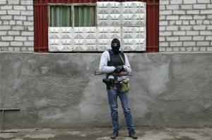 An armed man stands in front of the police headquarters building in Slaviansk