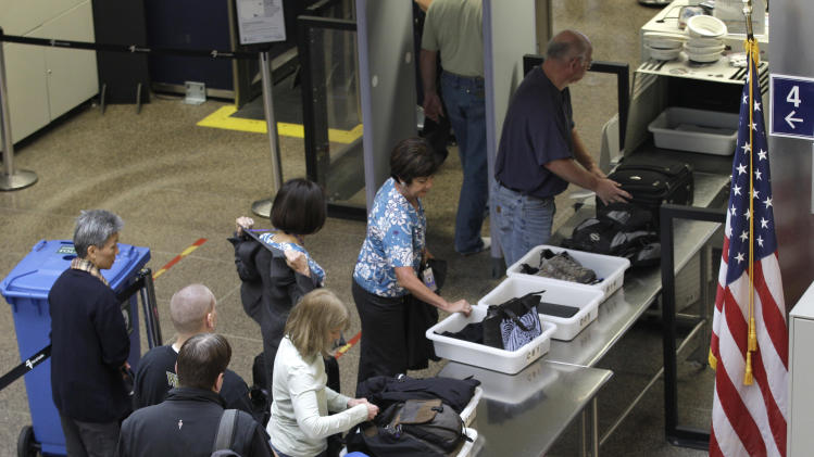 In this Nov. 19, 2010 photo, passengers prepare for security screening at the Seattle-Tacoma International Airport in Seattle. As passengers get ready to run the security check gantlet during some of the busiest flying days of the year, travel experts say dressing sensibly and packing wisely can help people breeze through screenings with their dignity intact. (AP Photo/Ted S. Warren)