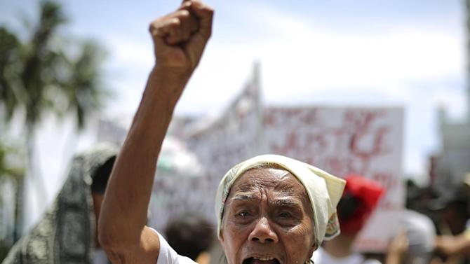 """Filipino Narcisa Claveria, 84, who claims to have been a sex slave during World War II, shouts slogans during a rally in front of the Japanese Embassy in Manila, Philippines Wednesday, June 25, 2014. A group of alleged Filipino """"comfort women"""" demanded recognition following the announcement of the affirmation of the Kono Statement as a result of the Japanese government investigation on the alleged WWII sexual slavery in Korea. (AP Photo/Aaron Favila)"""