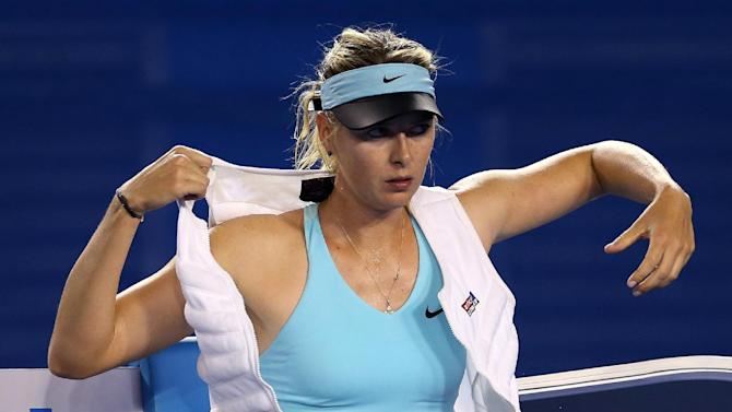 Maria Sharapova of Russia puts on ice vest between games as she plays Bethanie Mattek-Sands of the U.S. during their first round match at the Australian Open tennis championship in Melbourne, Australia, Tuesday, Jan. 14, 2014.(AP Photo/Rick Rycroft)