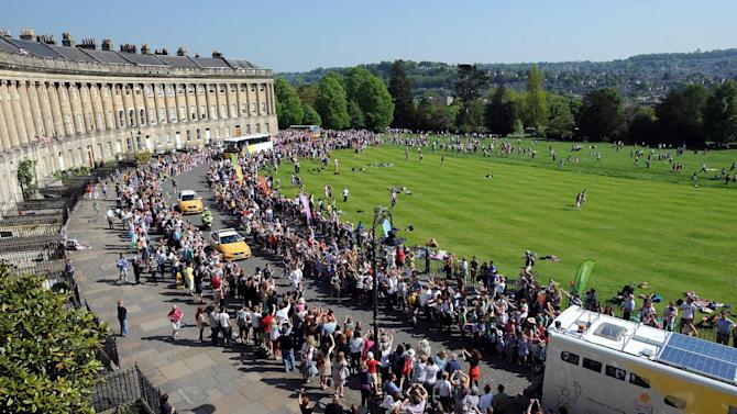 This photograph made available by LOCOG shows Christopher Phillips carrying the Olympic flame along The Royal Crescent, Bath, west England Tuesday May 22, 2012. The Olympic torch relay is on its fourth day as it traverses Britain ahead of the July 27 opening of the London Games. (AP Photo/Joe Ben Birchall/LOCOG)