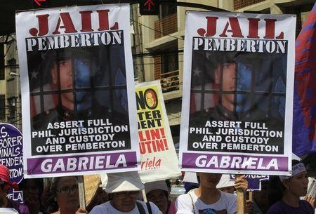 Activists display placards of U.S. Marine Private First Class Joseph Scott Pemberton during a protest outside the presidential palace in Manila