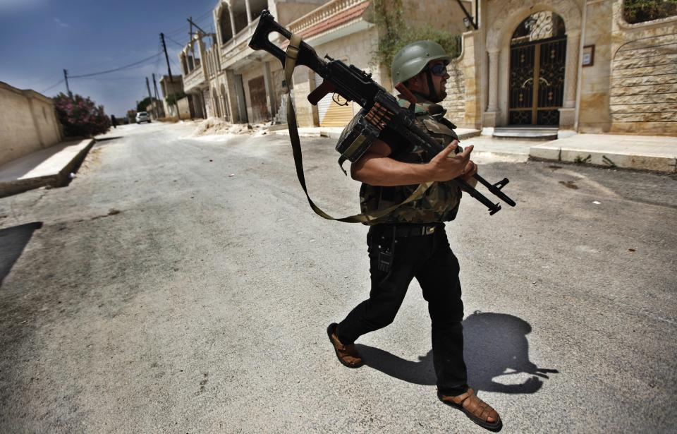 A Free Syrian Army fighter walks with his weapon during clashes with Syrian troops near Idlib, Syria, Friday, June 15, 2012. (AP Photo)