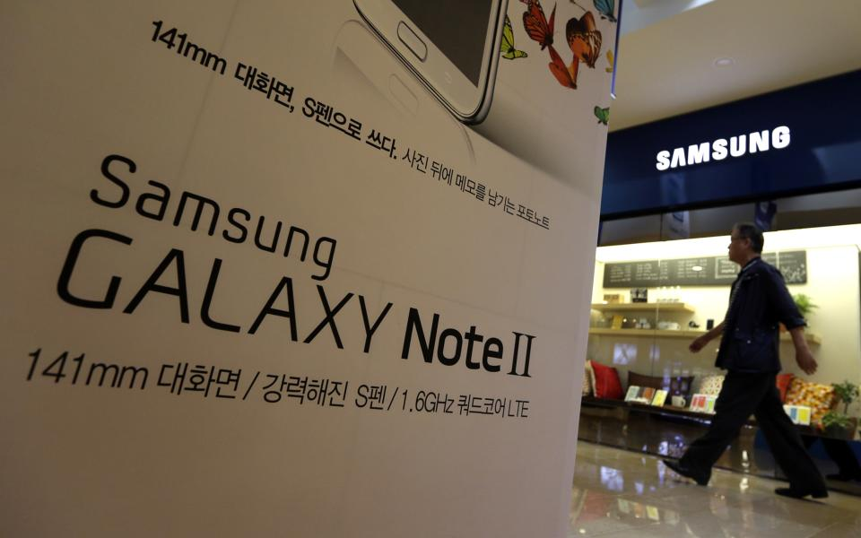 A man walks by a billboard of Samsung Electronics's Galaxy Note II at a showroom of its headquarters in Seoul, South Korea, Friday, Oct. 5, 2012. Samsung Electronics Co. tipped all-time high quarterly operating profit, likely driven by strong sales of high-end smartphones that offset weak semiconductor orders. (AP Photo/Lee Jin-man)