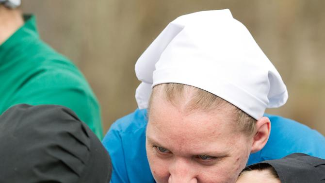 Anna Miller plays with her daughter during a farewell celebration outside the school house in Bergholz, Ohio on Tuesday, April 9, 2013.  The farewell celebration was held for Miller and other Amish members leaving for prison throughout the week for their roles in a hair and beard cutting scandal.  (AP Photo/Scott R. Galvin)