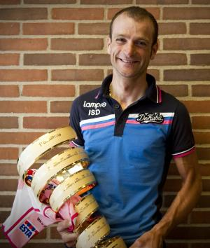 FILE - In this May 3, 2012 file photo Michele Scarponi shows the trophy of 2011 edition of the Giro d'Italia cycling race after Alberto Contador was stripped of the honor for doping, in Herning, Denmark. Extending the fallout from the Lance Armstrong doping report, at least 15 more cyclists are being linked to the American's banned physician in what is unfolding as an intricate scheme of money laundering, tax evasion and widespread doping. The Gazzetta dello Sport reports that former Giro d'Italia winners Michele Scarponi and Denis Menchov, plus this year's Olympic champion Alexandre Vinokourov, are under investigation for doping under the supervision of Dr. Michele Ferrari. (AP Photo/Gian Mattia D'Alberto, File)