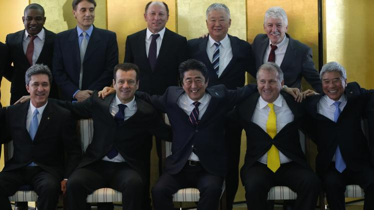 Japan's Prime Minister Shinzo Abe poses for a photo with former Brazilian soccer star Zico and Brazil's new coach Dunga during a meeting with Brazilian soccer players in Brasilia
