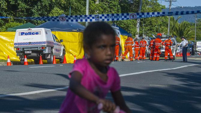 A local girl rides her bicycle past the scene of a stabbing attack at a home in Cairns