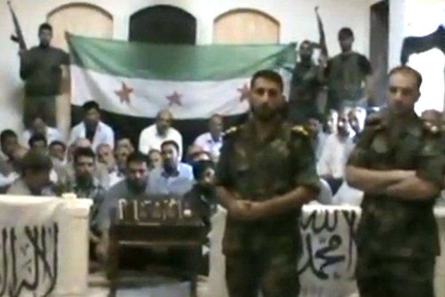 This image made from a video released by the Baraa Brigades and accessed Sunday, Aug. 5, 2012, purports to show Free Syrian Army soldiers guarding a group of Iranians abducted a day earlier and promising more attacks on Iranian targets in Damascus, Syria. Armed men in the video identify themselves as members of the rebel Baraa Brigades and say that at least one of the 48 captives was an officer of Irans powerful Revolutionary Guards. They claim that Iranians were on a reconnaissance mission in the capital Damascus at the time they were abducted. Iran says they are pilgrims who were visiting a shrine. (AP Photo/Baraa Brigades via AP video) THE ASSOCIATED PRESS IS UNABLE TO INDEPENDENTLY VERIFY THE AUTHENTICITY, CONTENT, LOCATION OR DATE OF THIS HANDOUT PHOTO