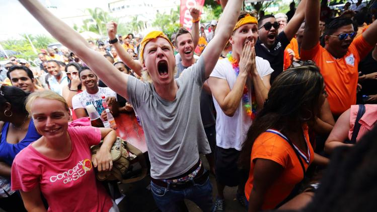 Fans supporting the Netherlands cheer after defeating Mexico 2-1 in a knockout match in the 2014 World Cup round of 16 game during, a public viewing area in Paramaribo