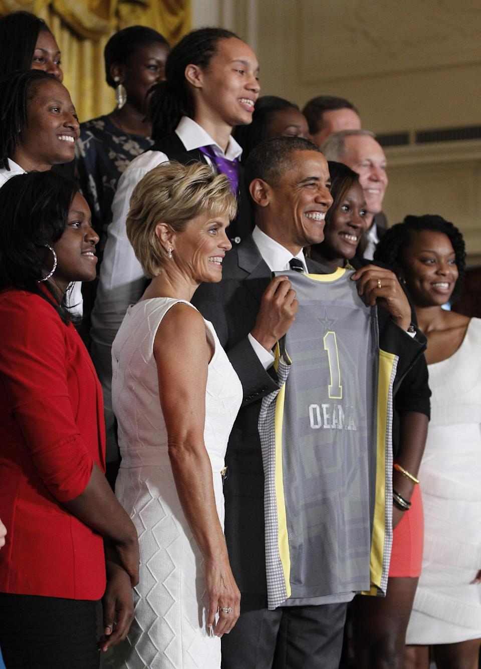 President Barack Obama, center, holds up a jersey given to him by members of the 2012 NCAA Women's basketball champions Baylor University Bears during a ceremony in the East Room of the White House in Washington, Wednesday, July 18, 2012. (AP Photo/Pablo Martinez Monsivais)