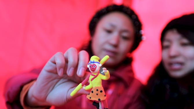 """Folk artist Ma Yueru makes a clay figurine of the """"Monkey King"""" also known as """"Sun Wukong"""" for visitors at a Spring Festival temple fair on the second day of the Chinese Lunar New Year of the Monkey in Beijing,"""