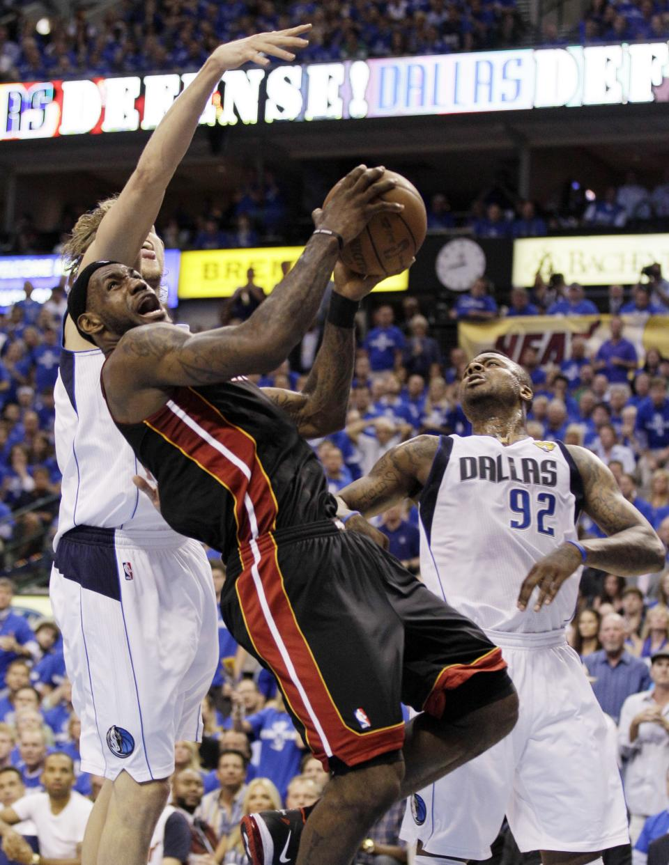 Miami Heat's LeBron James drives past Dallas Mavericks' Dirk Nowitzki and DeShawn Stevenson (92) during the first half of Game 5 of the NBA Finals basketball game Thursday, June 9, 2011, in Dallas. (AP Photo/Mark Humphrey)