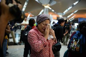 A woman reacts to news regarding a Malaysia Airlines …