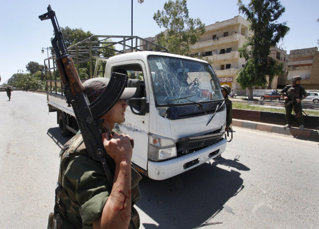 A Syrian army soldier secures the scene as he stands next to a military truck which was attacked by a roadside bomb, in Daraa city, southern Syria, on Wednesday May 9, 2012.  The explosion targeted th