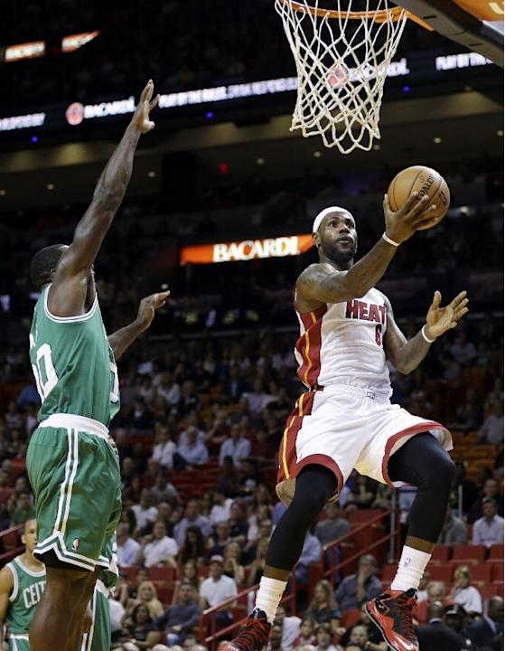 Miami Heat's LeBron James, right, shoots as Boston Celtics' Brandon Bass, left, defends during the first half of an NBA basketball game Saturday, Nov. 9, 2013, in Miami