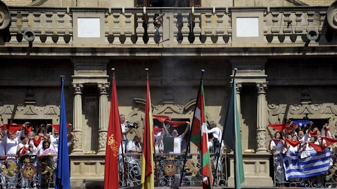A rocket signalling the beginning of the San Fermin festival is fired between the Basque and Spanish flags in Pamplona