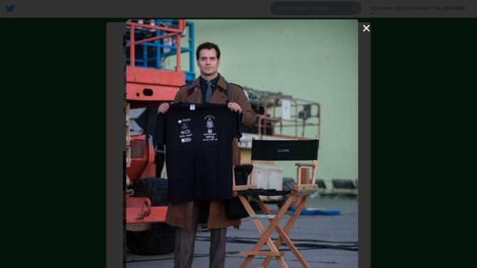 Henry Cavill, as Clark Kent, holds up a shirt in support of the Royal Marine Challenge.