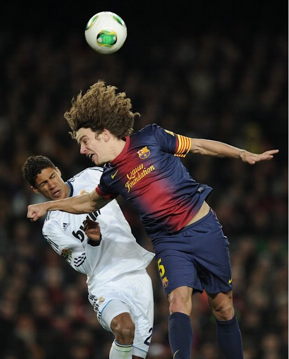 Carles Puyol (right) clashes with Real Madrid's Raphael Varane in a Spanish Cup match at Camp Nou on February 26, 2013
