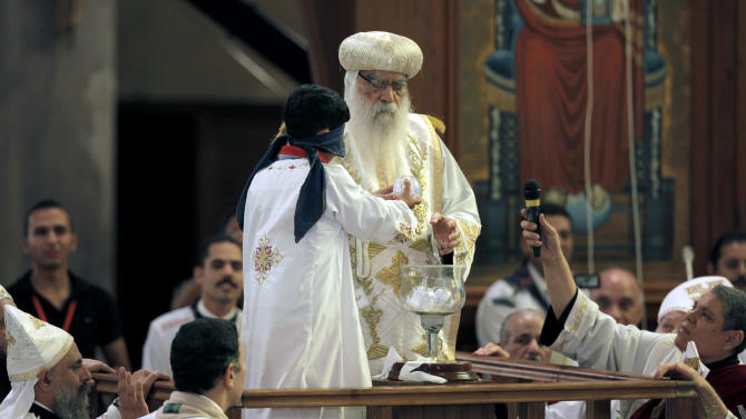 A blindfolded boy draws the name of the next patriarch from a crystal chalice next to acting Coptic Pope Pachomios, center, during the papal election ceremony at the Coptic Cathedral in Cairo, Egypt, Sunday, Nov. 4, 2012. Egypt's ancient Coptic Christian church chose a new pope in an elaborate Sunday ceremony meant to invoke the will of God, in which a blindfolded boy drew the name of the next patriarch from a crystal chalice. Bishop Tawadros will be ordained Nov. 18 as Pope Tawadros II, the spiritual leader of a community that increasingly fears for its future amid the rise of Islamists to power in the wake of the 2011 ouster of longtime authoritarian leader Hosni Mubarak.(AP Photo/Nasser Nasser)
