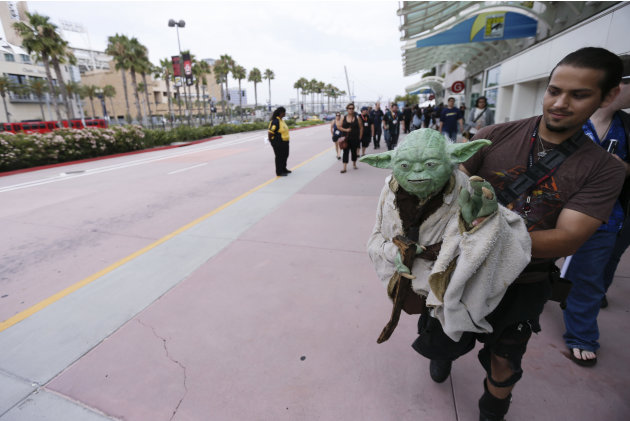 Chrys Petrone holds a Yoda figure as he walks along the entrance to Comic-Con Wednesday, July 11, 2012, in San Diego. The annual comic book and popular arts convention attracts over 100,000 people and