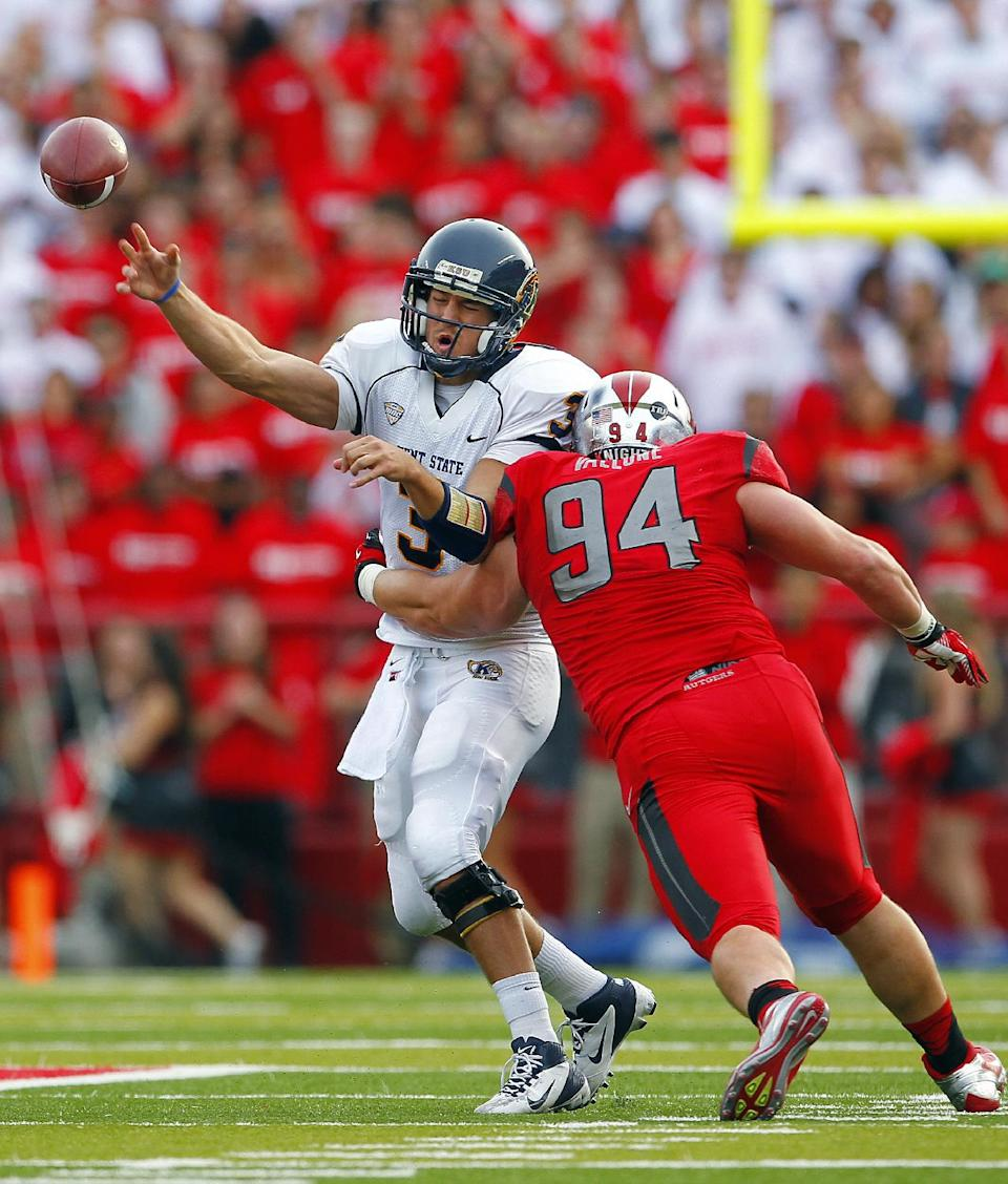 Kent State quarterback Spencer Keith (3) passes while under pressure from Rutgers' Scott Vallone (94) during the first half of an NCAA college football game in Piscataway, N.J., Saturday, Oct. 27, 2012. (AP Photo/Rich Schultz)