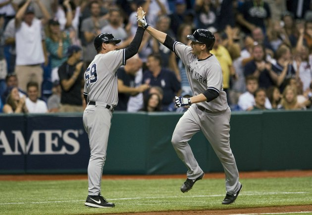 Yankees third base coach Thomson celebrates with Overbay after his solo home run off Rays' Lueke during MLB game in St. Petersburg