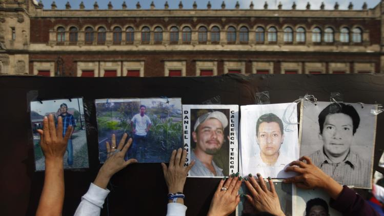 Women from the Caravan of Central American Mothers put up photos of missing migrants during a march in front of the National Palace in Mexico City