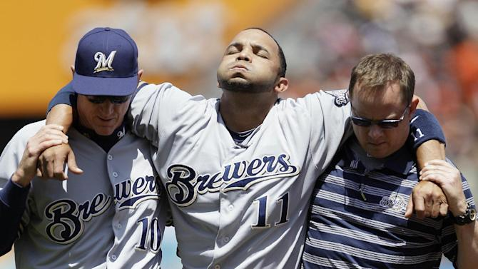 Milwaukee Brewers' Alex Gonzalez (11) is helped off the field by manager Ron Roenicke (10) and trainer Dan Wright during the second inning of a baseball game against the San Francisco Giants in San Francisco, Saturday, May 5, 2012. Gonzalez was injured stealing second base and left the game. (AP Photo/Jeff Chiu)