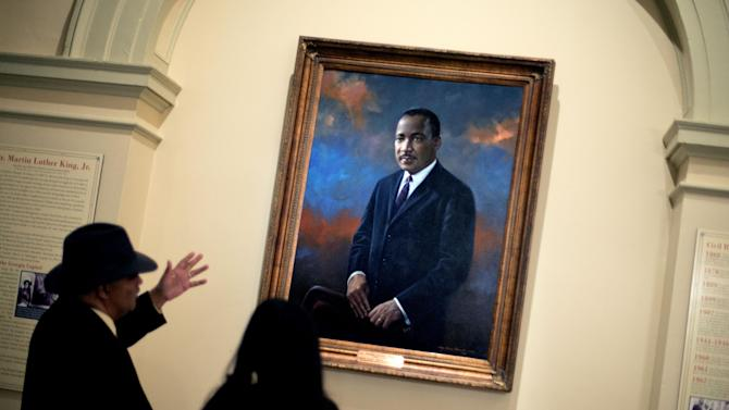 Rep. Roger Bruce, D-Atlanta, left, points out the hanging portrait of Rev. Martin Luther King Jr., to his assistant, Sophia Andrade, following a service celebrating King's birthday inside the Georgia State Capitol, Thursday, Jan. 17, 2013, in Atlanta. (AP Photo/David Goldman)