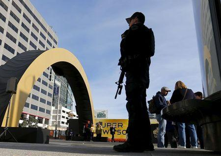 An armed police stands watch near a Super Bowl 50 attraction in down town San Francisco