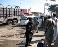 Pakistani security officials examine the site of a suicide bombing in Khar, the main town of Bajaur district. A teenage suicide bomber targeted police in a bustling Pakistan town square on Friday, killing at least 24 people and wounding dozens in the tribal area near the Afghan border, officials said