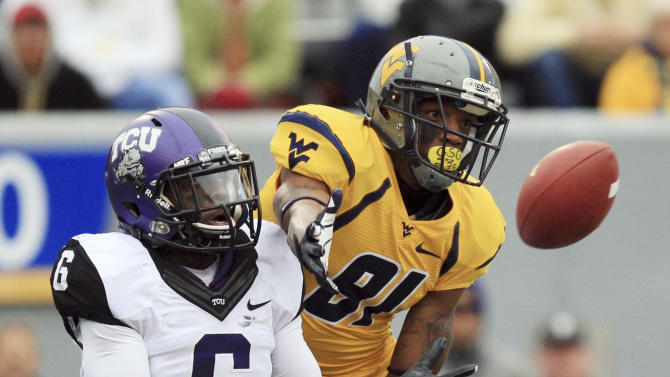 West Virginia wide receiver J.D. Woods (81) catches a touchdown pass in front of TCU safety Elisha Olabode (6) during the first half of their NCAA college football game in Morgantown, W.Va., on Saturday, Nov. 3, 2012. (AP Photo/Christopher Jackson)
