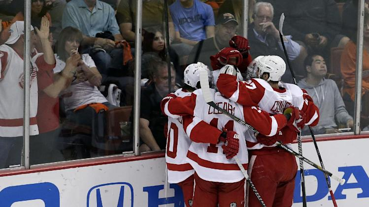 Detroit Red Wings team members celebrate a goal by Henrik Zetterberg as Anaheim Ducks goalie Jonas Hiller, left, kneels on the ice during the first period in Game 7 of their first-round NHL hockey Stanley Cup playoff series in Anaheim, Calif., Sunday, May 12, 2013. (AP Photo/Chris Carlson)