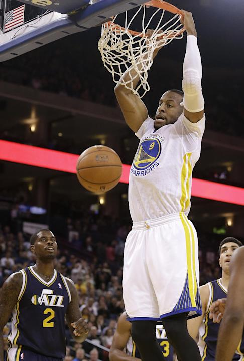Golden State Warriors small forward Andre Iguodala (9) dunks over Utah Jazz power forward Marvin Williams (2) and others during the second quarter of an NBA basketball game in Oakland, Calif., Saturda