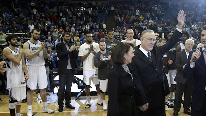 Minnesota Timberwolves head coach Rick Adelman, right, waves to the crowd as players applaud after he becomes the eighth coach in the NBA to win 1,000 games after defeating the Detroit Pistons in their basketball game, Saturday, April 6, 2013, in Minneapolis. The Timberwolves won 107-101. Accompanying him is his wife, Mary Kay.  (AP Photo/Jim Mone)